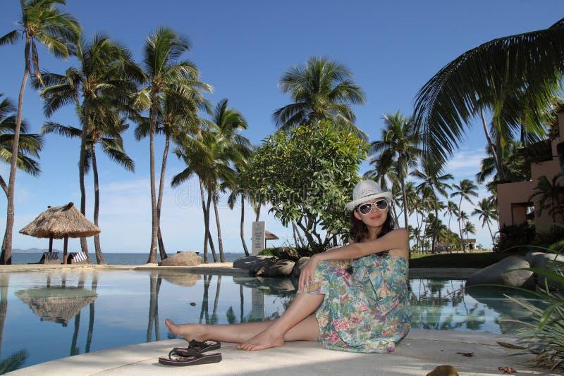 Una muchacha asiática en un centro turístico tropical fotos de archivo