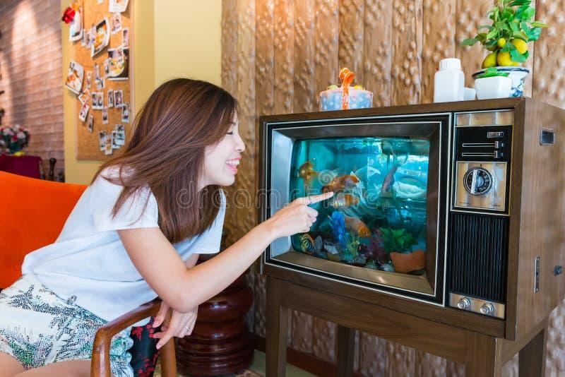 Una muchacha asiática está jugando con el pez de colores en el acuario de la TV imagen de archivo