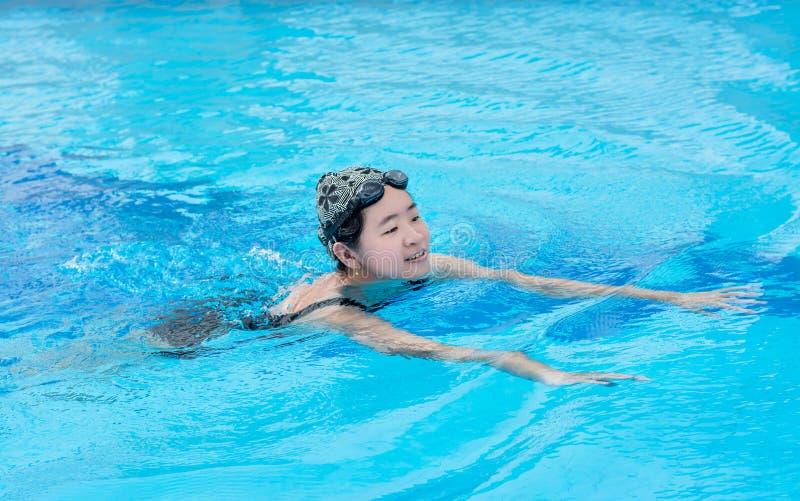 Una muchacha asiática está nadando en la piscina fotografía de archivo libre de regalías
