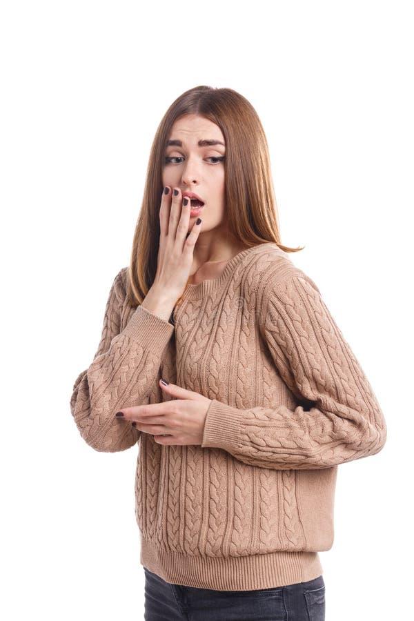 Una muchacha asustada frightenedly que cubre su mano con su boca abierta y que mira abajo Aislado emociones imagen de archivo libre de regalías