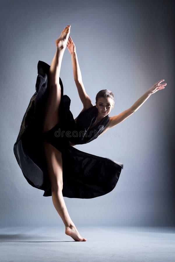 Una muchacha atlética hermosa en un vestido negro está bailando En el salto fotografía de archivo libre de regalías