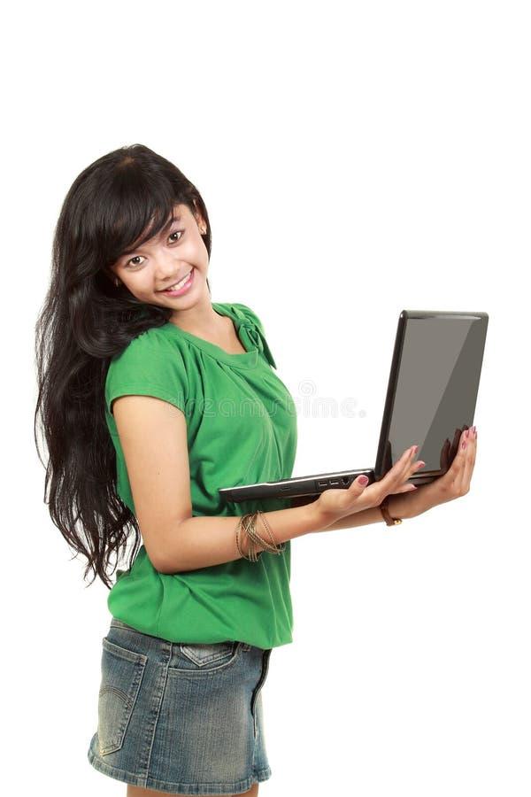 Una muchacha atractiva con una computadora portátil fotografía de archivo