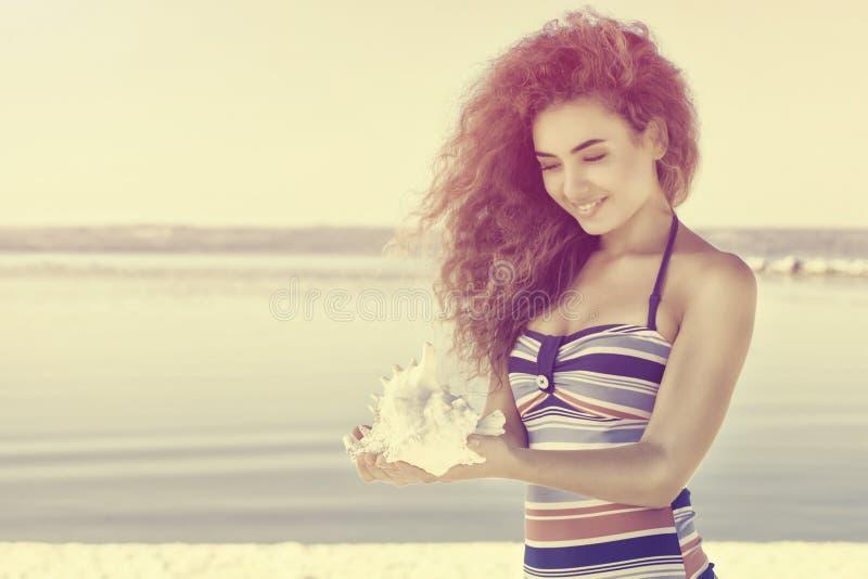 Una muchacha atractiva joven en un traje de baño rayado colorido lleva a cabo una cáscara grande, blanca foto de archivo