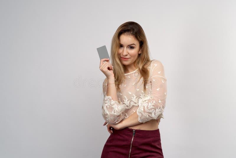 Una muchacha atractiva joven mira impresionante la cámara, sosteniendo una tarjeta de banco plástica de crédito delante de su man imágenes de archivo libres de regalías