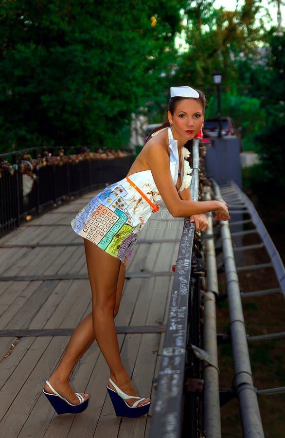Una muchacha atractiva seria se coloca en el puente se inclina para él en un vestido de papel de moda que mira la cámara fotos de archivo