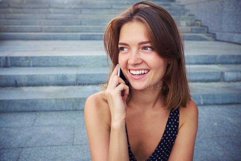Una muchacha atractiva tiene conversación bastante animada sobre su p elegante imagen de archivo