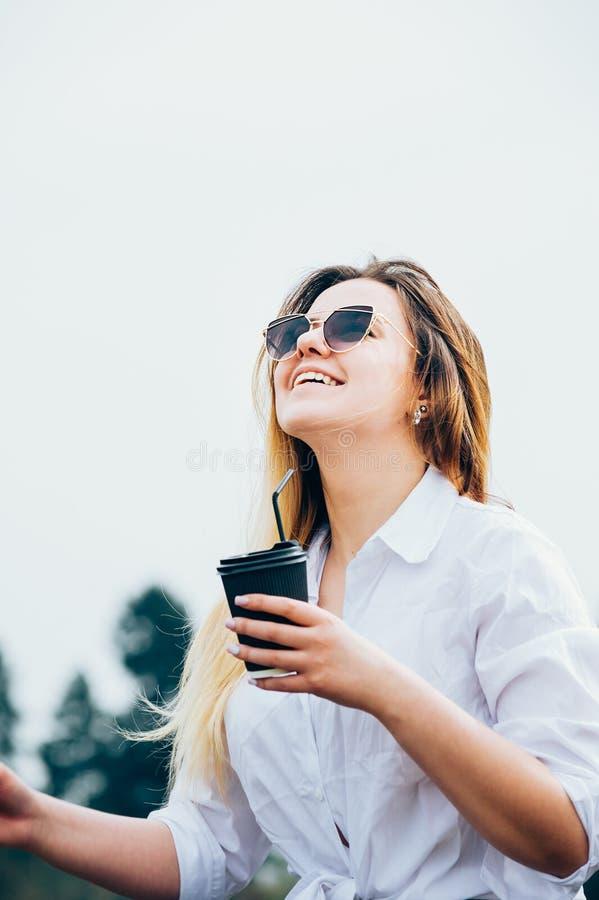 Una muchacha bastante de pelo largo en gafas de sol con una bebida, sonriendo foto de archivo libre de regalías