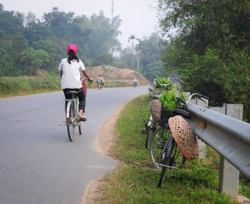 Una muchacha biking en el camino rural en Yenbai, Vietnam imagenes de archivo