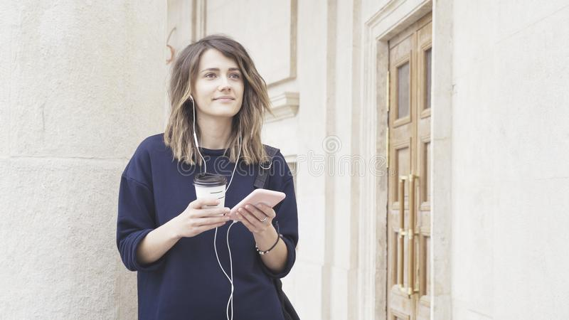 Una muchacha blanca morena sonriente está escuchando la música al aire libre imagen de archivo libre de regalías