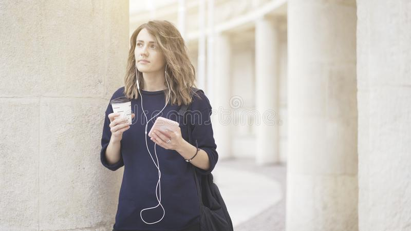 Una muchacha blanca morena sonriente está escuchando la música al aire libre foto de archivo