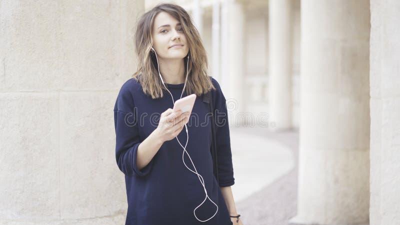 Una muchacha blanca morena sonriente está escuchando la música al aire libre fotografía de archivo libre de regalías