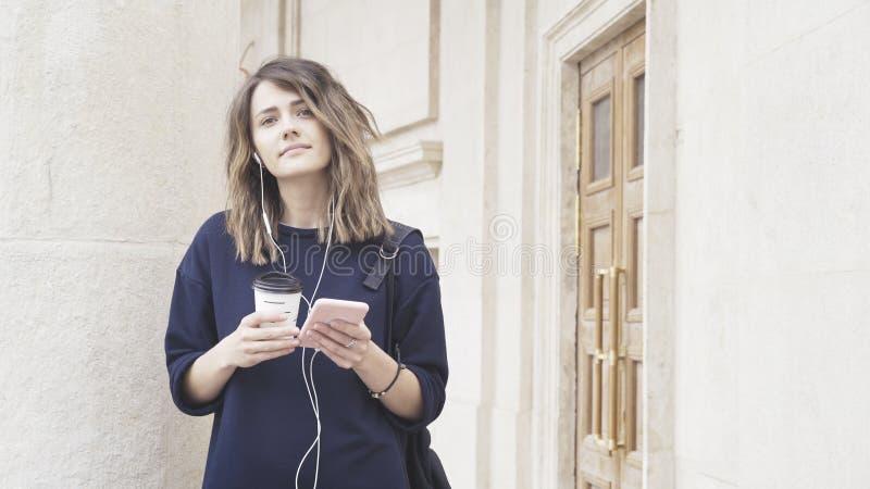 Una muchacha blanca morena sonriente está escuchando la música al aire libre imágenes de archivo libres de regalías