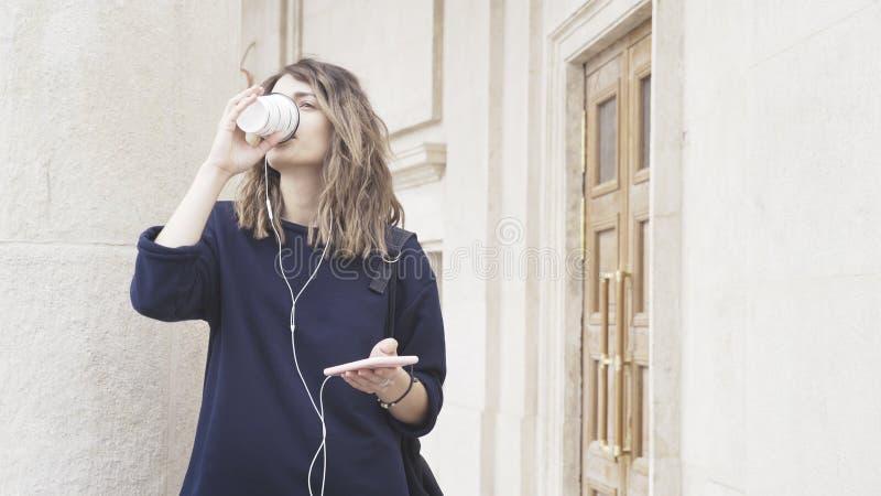 Una muchacha blanca morena sonriente está escuchando la música al aire libre fotos de archivo