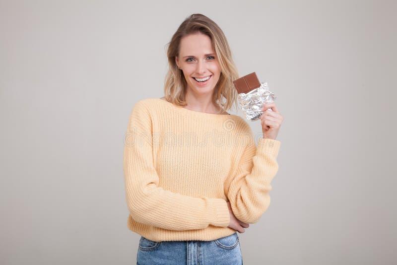 Una muchacha blanda joven hermosa con el pelo rubio sostiene una barra de chocolate en la cara que ella est? llevando en un su?te foto de archivo