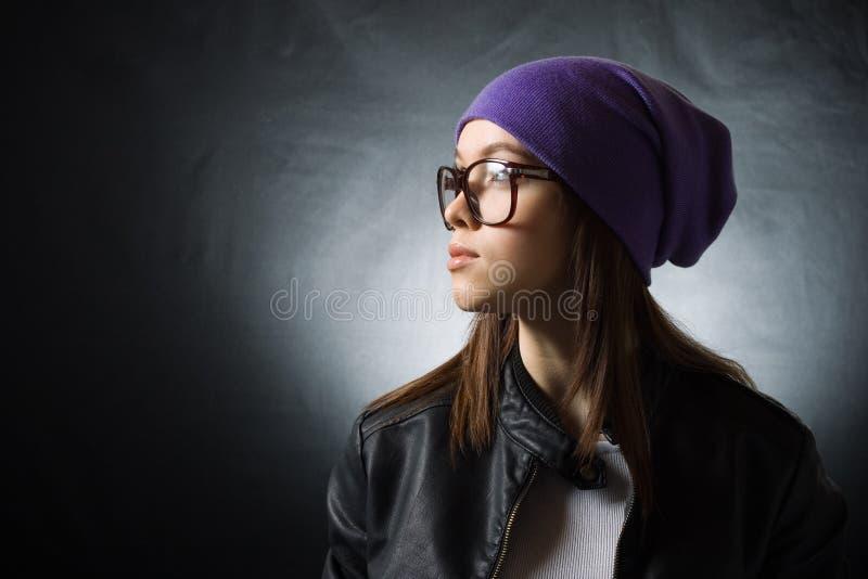 Una muchacha bonita en un sombrero hecho punto púrpura fotografía de archivo