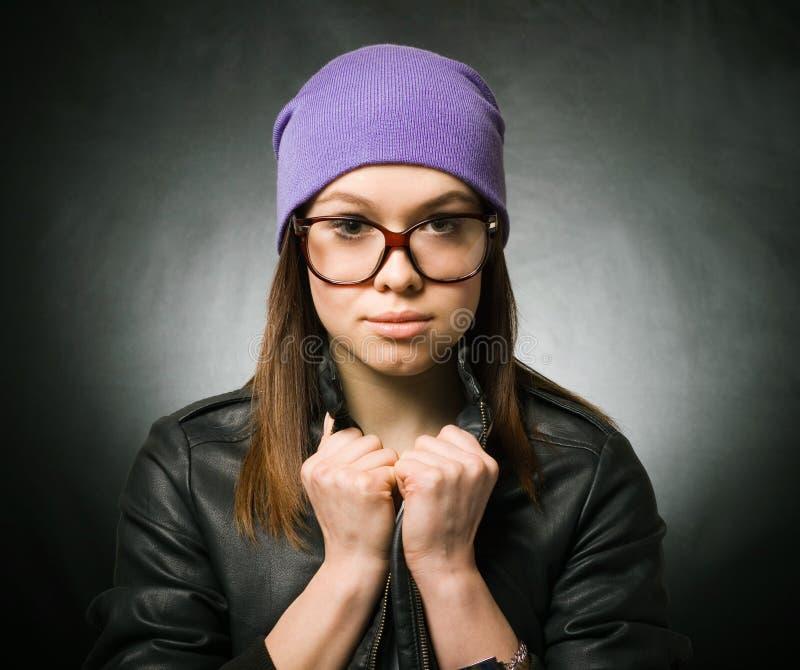 Una muchacha bonita en un sombrero hecho punto púrpura foto de archivo libre de regalías