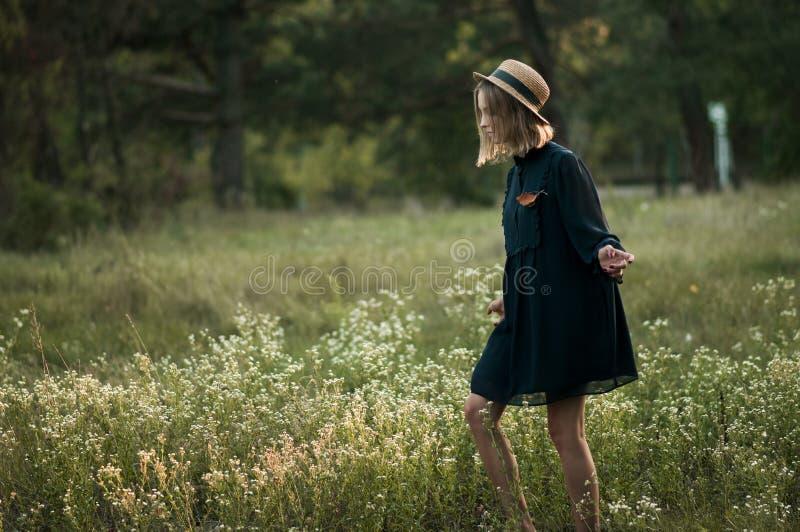 Una muchacha bonita está caminando a lo largo del campo de flor imagenes de archivo