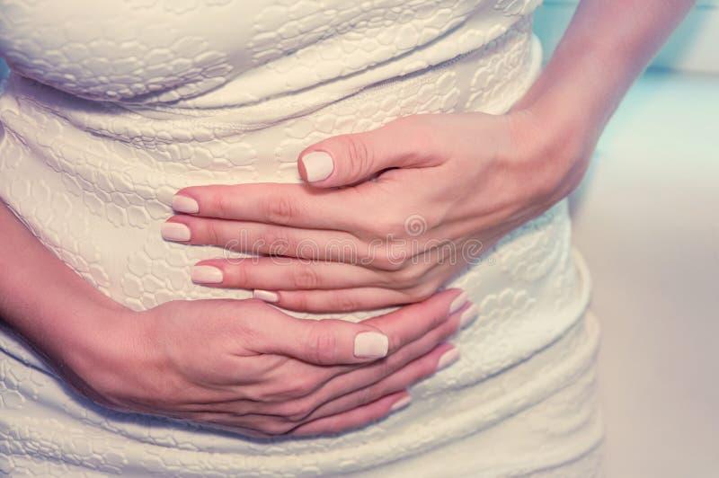 Una muchacha bronceada lleva a cabo sus manos a su estómago Concepto de IVF, embarazo, digestión, salud del sistema reproductivo  imagen de archivo libre de regalías