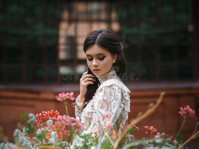 Una muchacha camina en un jardín floreciente, ella tiene una blusa del vintage con un arco, pelo largo de la castaña ella cuida s fotografía de archivo libre de regalías