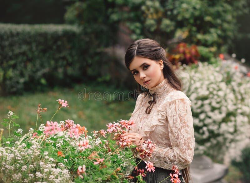 Una muchacha camina en un jardín floreciente, ella tiene una blusa del vintage con un arco, pelo largo de la castaña ella cuida s imagen de archivo