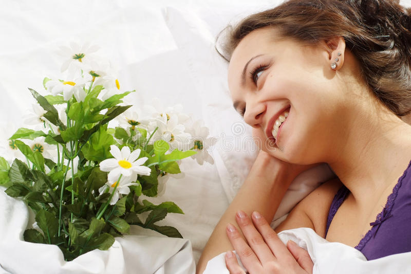 Una muchacha caucásica hermosa con una flor en una cama foto de archivo