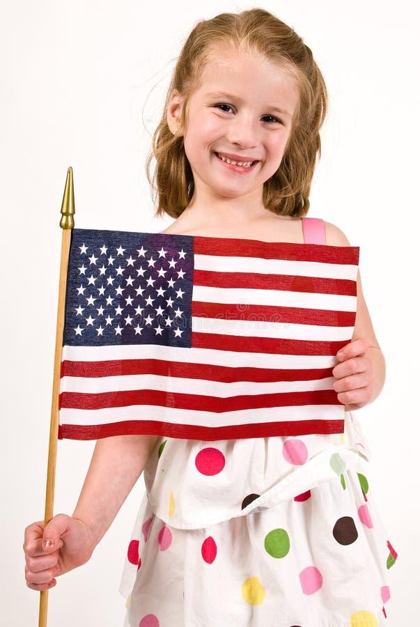 Muchacha caucásica joven que sostiene una bandera americana foto de archivo