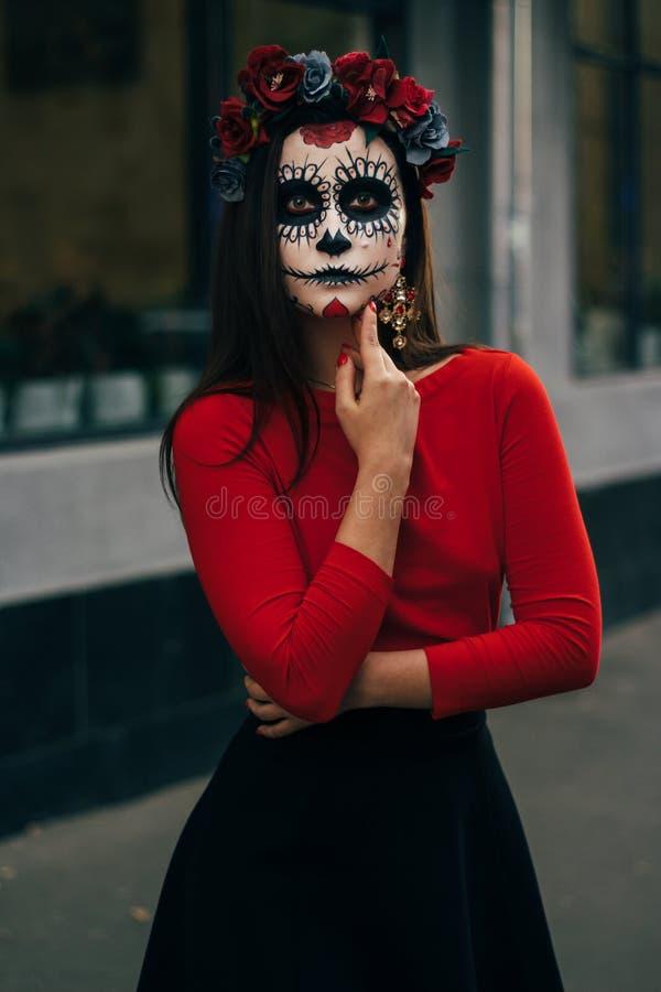 una muchacha con una cara pintada de un esqueleto, zombi muerto, en la ciudad durante el día día de todas las almas, día de los m fotos de archivo libres de regalías