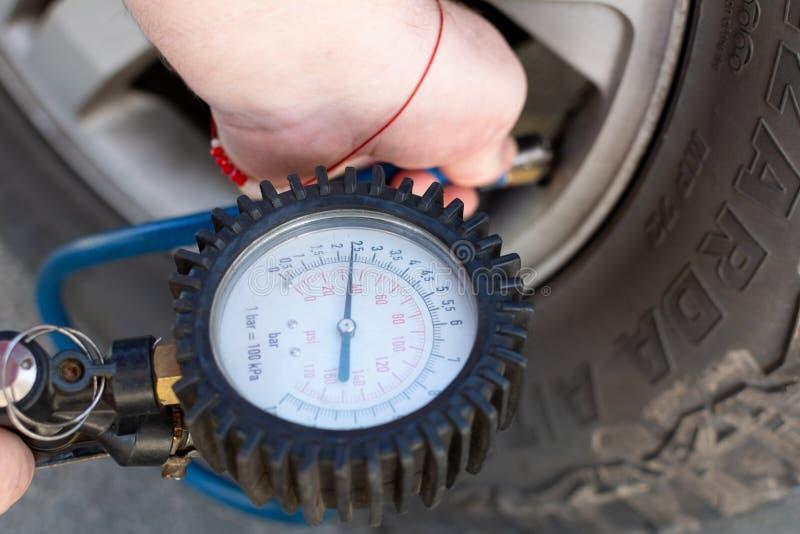 Una muchacha con una chuchería roja en sus de mano de las bombas neumáticos para arriba con un compresor para los neumáticos de b imagen de archivo