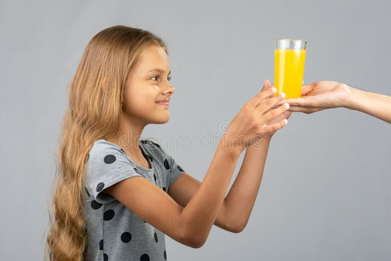 Una muchacha con dos manos toma un vidrio de jugo de la mano de otra persona foto de archivo