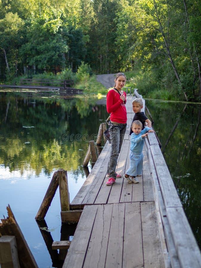 Una muchacha con dos niños se está colocando en el puente de madera viejo a través de un río reservado imagen de archivo