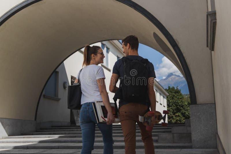 Una muchacha con el bolso y libros y un muchacho con la mochila y un patín que camina a la escuela después de vacaciones de veran fotos de archivo