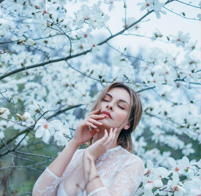 Una muchacha con el pelo justo, en una bata transparente que presenta contra un fondo de la floración, magnolia blanca Primavera, imagen de archivo libre de regalías