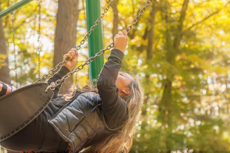 Una muchacha con el pelo largo que balancea en un oscilación en un parque del otoño foto de archivo libre de regalías