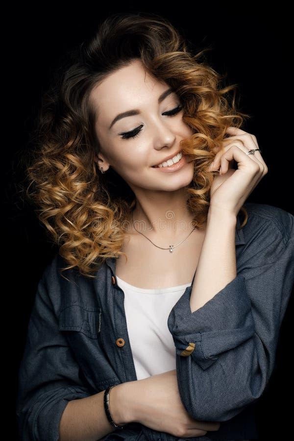 Una muchacha con el pelo rizado y una sonrisa amplia que lleva una camisa blanca y una blusa azul en fondo negro imagen de archivo