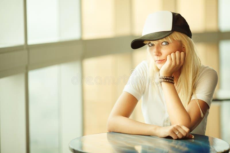 Una muchacha con el pelo rubio que se sienta en la tabla una mujer joven en una gorra de béisbol y con explosiones arregladas fotografía de archivo libre de regalías