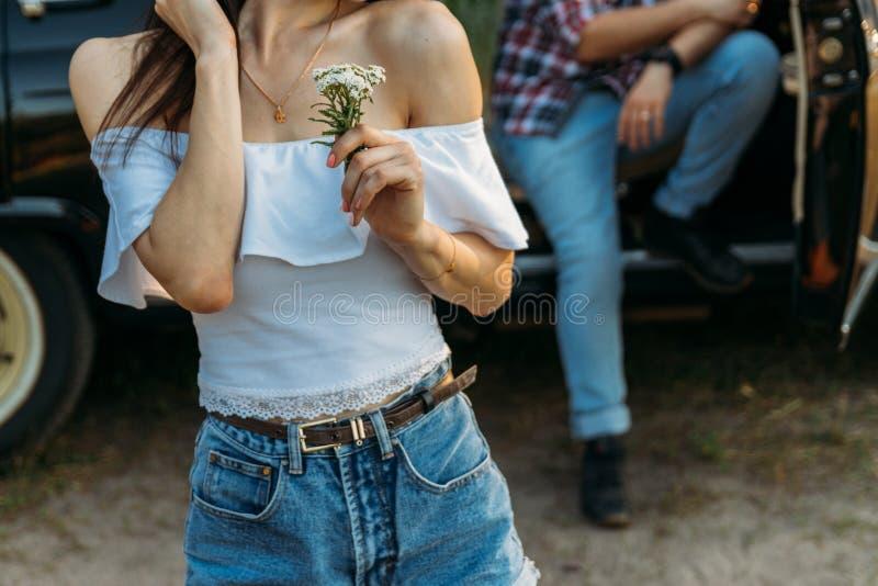 Una muchacha con una flor y en una blusa blanca, un hombre en una camisa de tela escocesa se está sentando en la parte de atrás d imagen de archivo libre de regalías