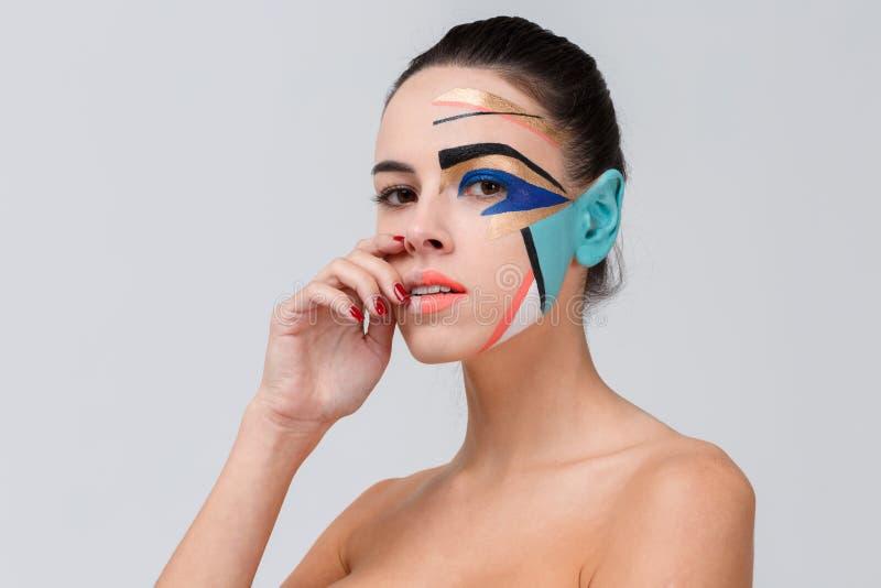 Una muchacha, con hombros desnudos y un maquillaje geométrico creativo en su cara fotos de archivo