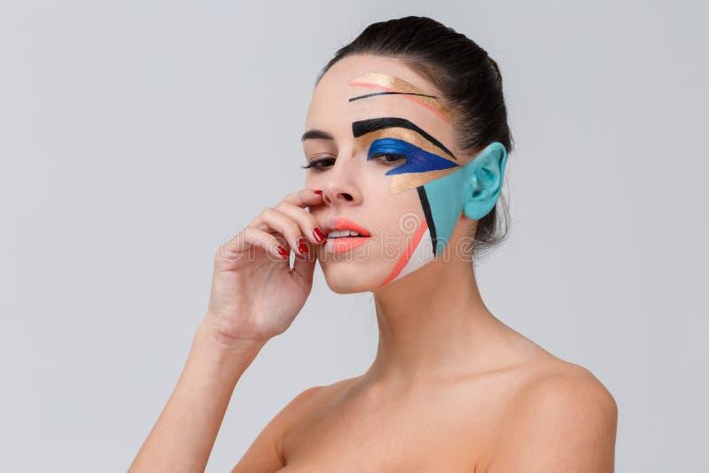 Una muchacha con hombros desnudos y un maquillaje geométrico creativo en su cara mira abajo fotos de archivo libres de regalías