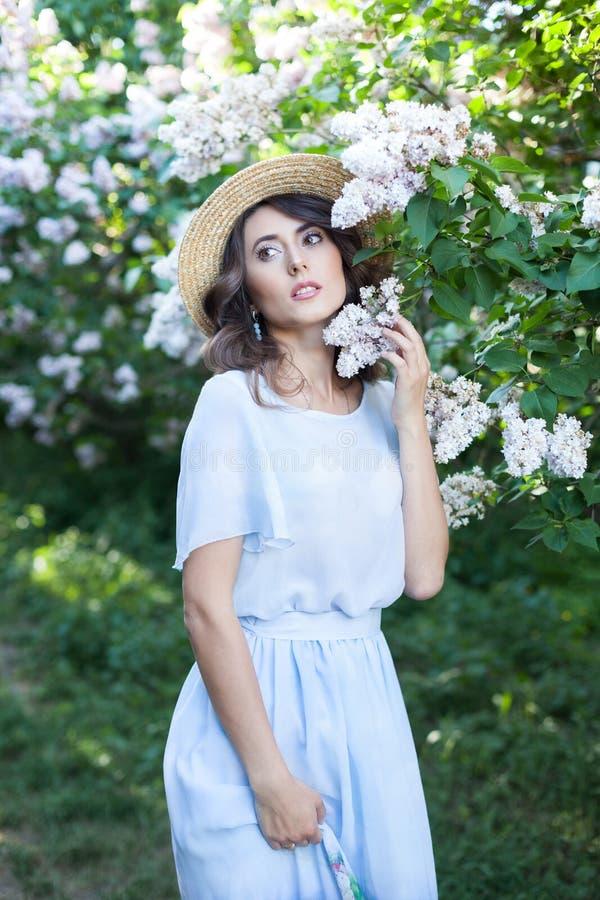 Una muchacha con la piel clara y el pelo marrón ondulado en un sombrero de paja en un jardín de la lila en la floración Retrato t fotos de archivo libres de regalías