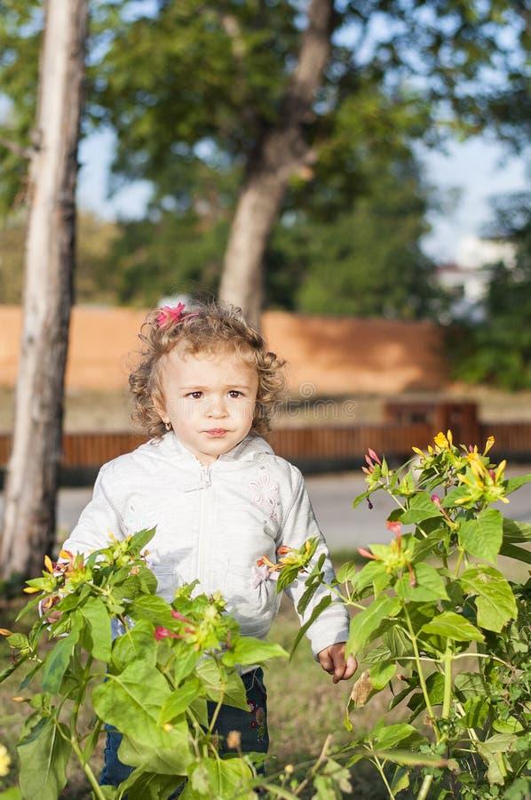 Una muchacha con las flores en el parque imagenes de archivo