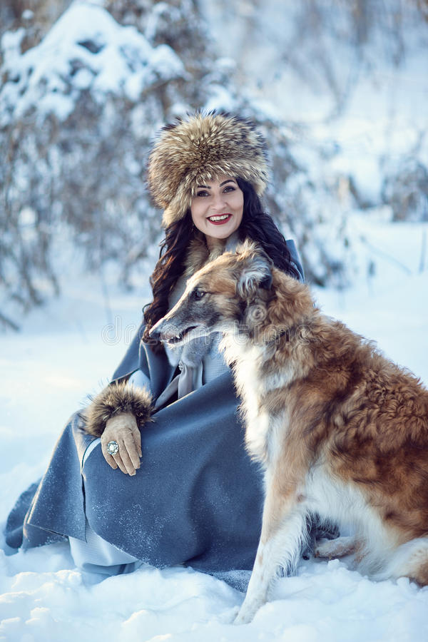 Una muchacha con los galgos en la nieve fotos de archivo libres de regalías