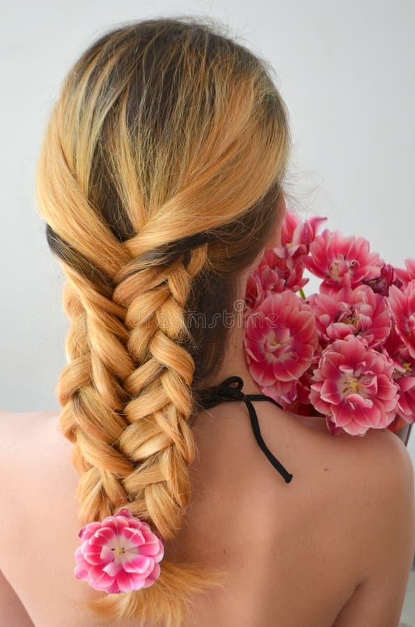 Una muchacha con los hairdress hermosos con un ramo de tulipanes es una clase de Columbus fotografía de archivo