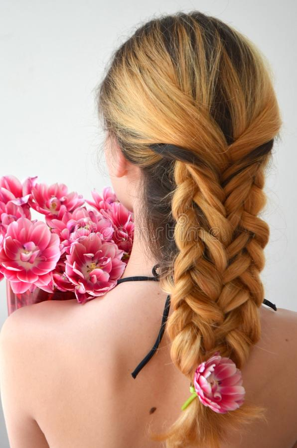 Una muchacha con los hairdress hermosos con un ramo de tulipanes es una clase de Columbus foto de archivo libre de regalías