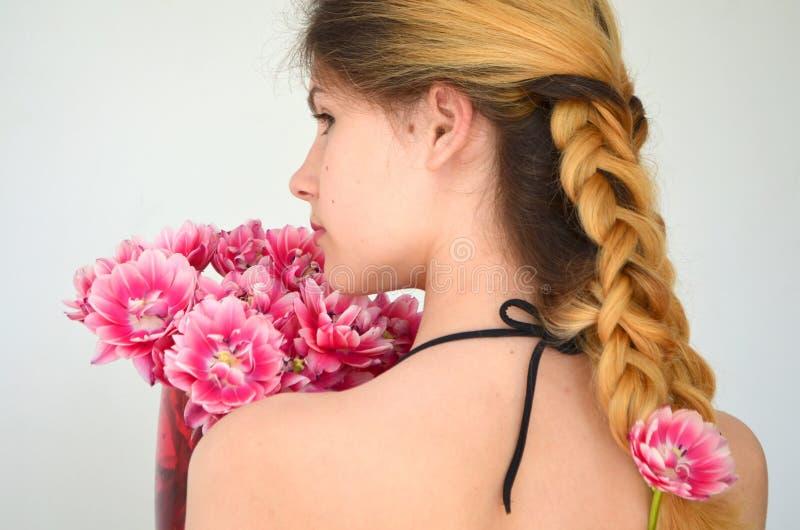 Una muchacha con los hairdress hermosos con un ramo de tulipanes es una clase de Columbus fotos de archivo