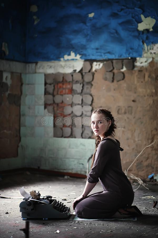 Una muchacha con los libros viejos en la casa vieja foto de archivo libre de regalías