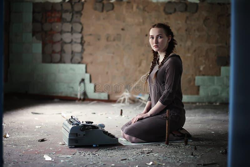 Una muchacha con los libros viejos en la casa vieja imagen de archivo