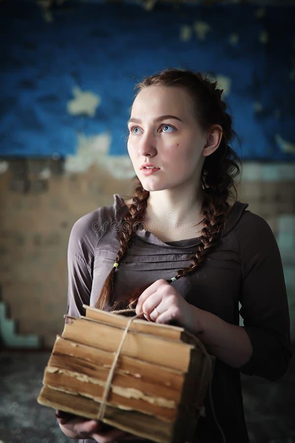 Una muchacha con los libros viejos en la casa vieja fotografía de archivo