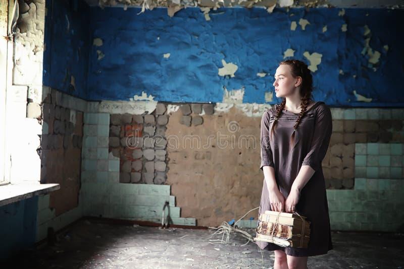 Una muchacha con los libros viejos en la casa vieja imagenes de archivo