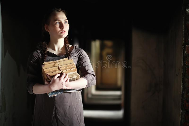 Una muchacha con los libros viejos en la casa vieja imágenes de archivo libres de regalías