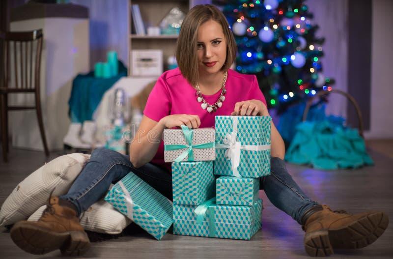 Una muchacha con los regalos y el árbol de navidad del Año Nuevo en el fondo imágenes de archivo libres de regalías